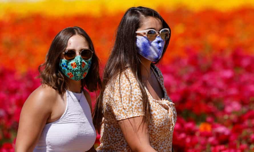 Women wear face masks and sunglasses outdoors in public. Some are reluctant to give up the face covering.