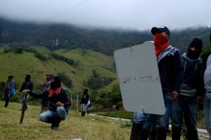 Kokonuko members hold makeshift shields as they face up to riot police at Aguas Tibias. The activists say public security forces are using live rounds as well as tear gas and rubber bullets. On 10 October, one indigenous journalist, Efigenia Vásquez, was shot and killed and two other Kokonuko were wounded. The shooter has not been identified.