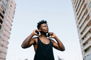 Confident Black Man With HeadphonesFrom below view of young African-American man wearing headphones and looking away on street.