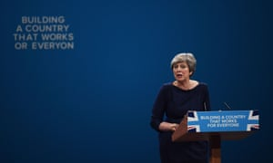 Letters begin to fall off the backdrop as Theresa May delivers her keynote speech.