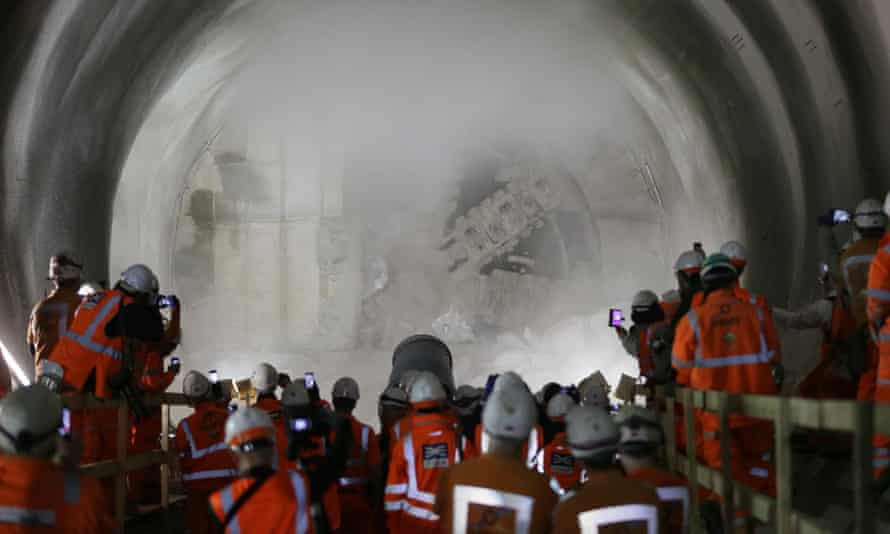 Workers watch and take pictures as a tunnel boring machine breaks into the eastern end of Liverpool Street Crossrail tunnel