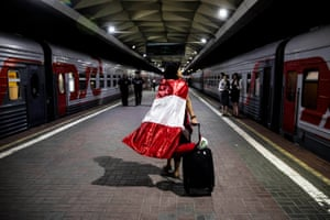 A woman with a Peruvian flag at Moscow's Leningradsky station boards a train for Saint Petersburg.