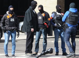 Hooded Belgian police officers patrol outside the Gare du Midi train station in Brussels