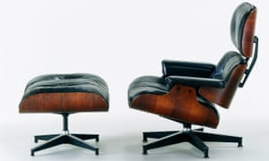 An Eames lounge chair and ottoman made from molded rosewood plywood with black leather upholstery and aluminium