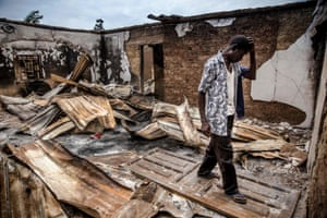 An Adara farmer visits an area of destroyed and burned houses