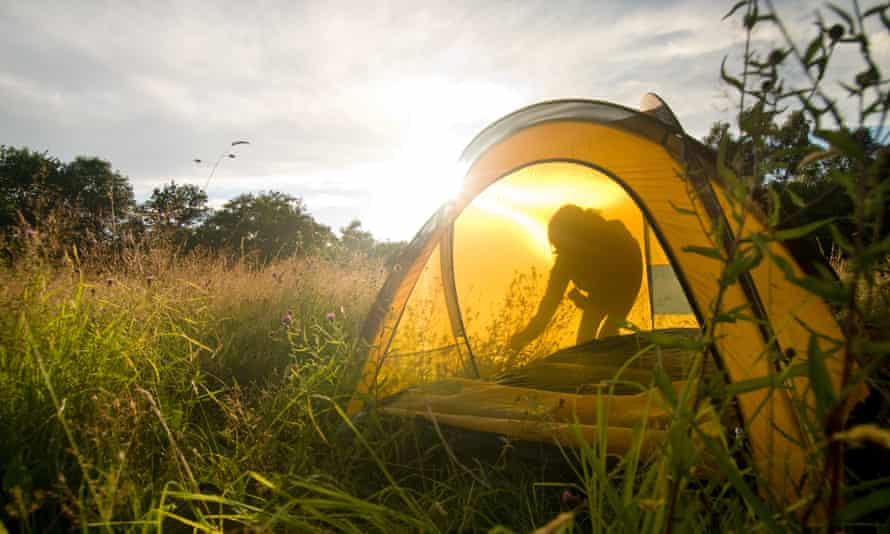 Person setting up tent in a meadow