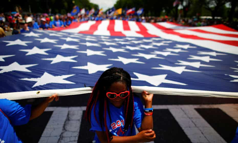 A girl helps carrying a US flag as she takes part in a parade during Fourth of July Independence Day celebrations in Washington DC.
