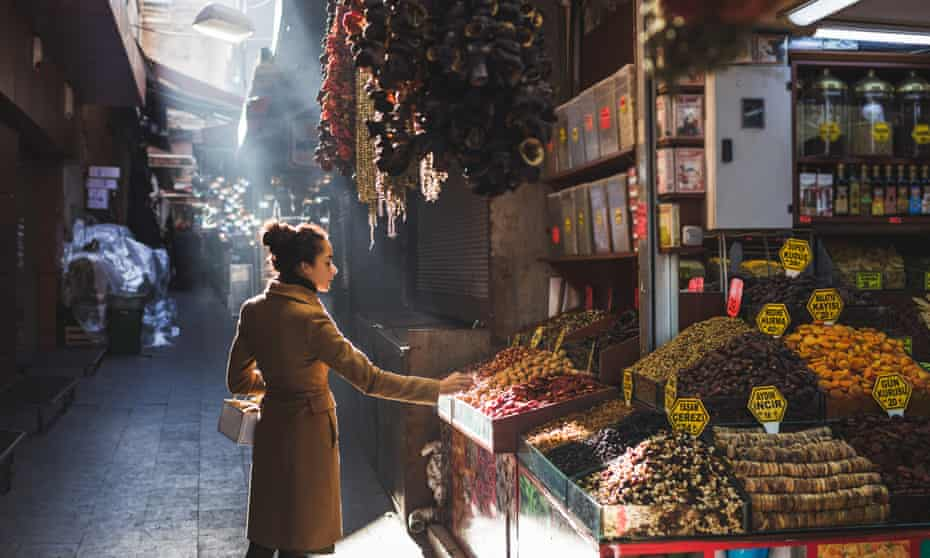 A woman chooses in the nuts and dried fruit stall in the market