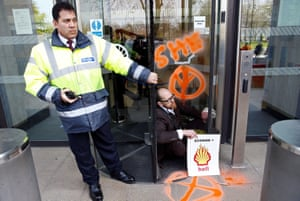 A climate change activist is seen with his hands glued to the entrance of the Shell Centre