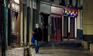 A woman walks on a deserted street in Montmartre before the 8pm curfew throughout Paris
