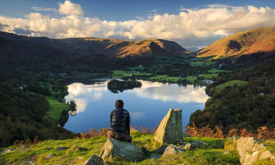 A walker admires the view of Grasmere from Loughrigg Hill.