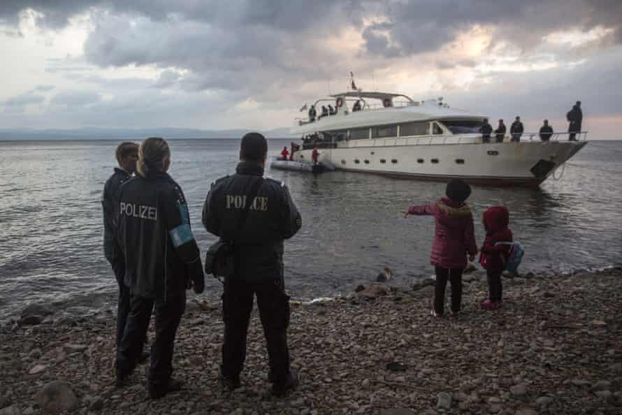 Frontex security personnel watch refugees and migrants disembarking from a yacht on Lesbos.
