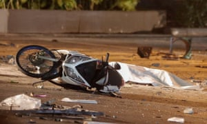 A body lies covered on the ground between damaged motorcycles at the scene of the explosion. Thais, Chinese and one Filipino are among the dead, officials have said