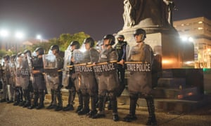 Police officers stand together in a line to alter the movement of demonstrators in Louisville, Kentucky, on 23 September.