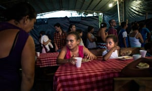 People have dinner at the shelter for the displaced community of El Castaño.