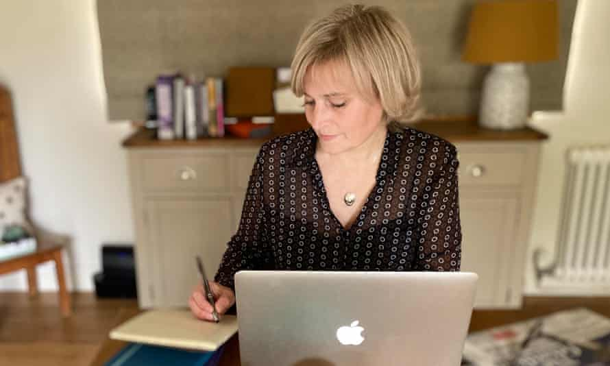 Elisabeth Ribbans working frm home, with her laptop in front of her, making notes on a notepad