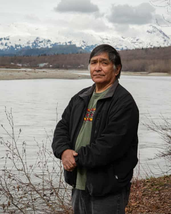 Jones Hotch, Klukwan elder on the banks of the Chilkat River with the village of Klukwan in the distance