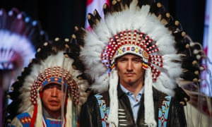 Prime Minister Justin Trudeau poses after receiving a ceremonial headdress while visiting the Tsuut'ina First Nation near Calgary, Alberta, Friday, March 4, 2016. (Jeff McIntosh/The Canadian Press via AP)