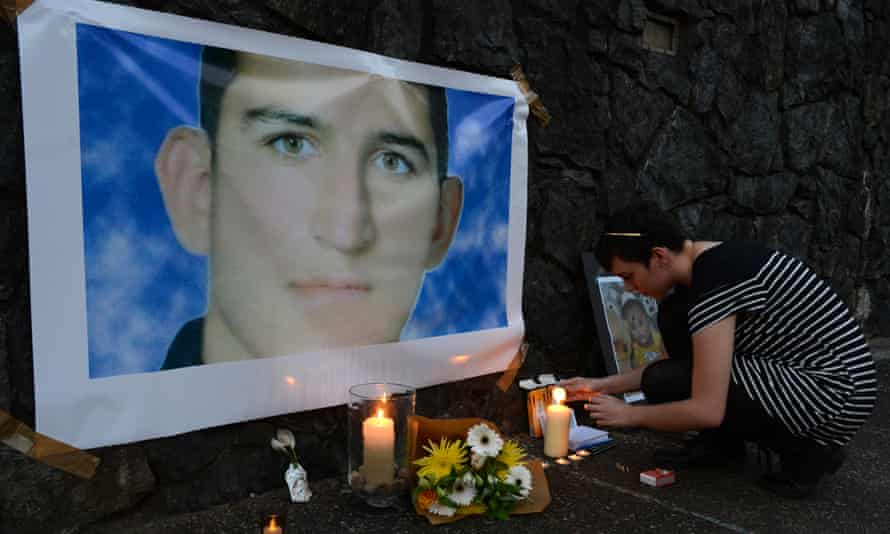 A woman lights a candle for Reza Barati during a vigil in support of asylum seekers in Brisbane, 23 February 2014.