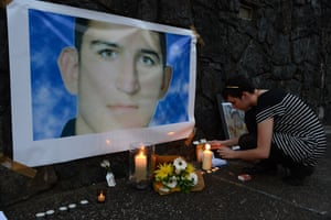 A woman lights a candle in a shrine for Reza Barati during a vigil in support of asylum seekers in Brisbane, Sunday, Feb. 23, 2014. The nation wide vigil was held in response to the death of 23-year-old Iranian man Reza Barati who died while in a detention centre on Manus Island on February 18.