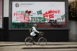 A cyclist passes an image of a blank mock tweet by Jeremy Corbyn, covered in anti-Brexit and People's Vote graffiti, in north London