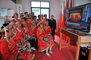 People of she ethnic group watch a live broadcast of the opening ceremony in Shangrao in Jiangxi province