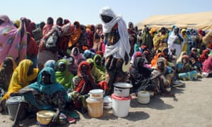 Women and children wait for food at a refugee camp in Borno state, north-east Nigeria.