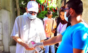 A staff member sprays disinfectant on the hands of a voter during the parliamentary elections in Damascus, capital of Syria, on July 19, 2020. Credit: Xinhua/REX/Shutterstock
