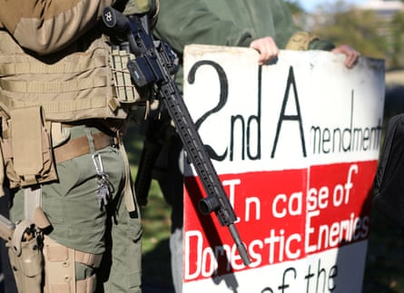 """A man carries a rifle as militia members and pro-gun rights activists participating in a """"Declaration of Restoration"""" rally prepare to march to Washington DC from Arlington, Virginia, on 9 November."""