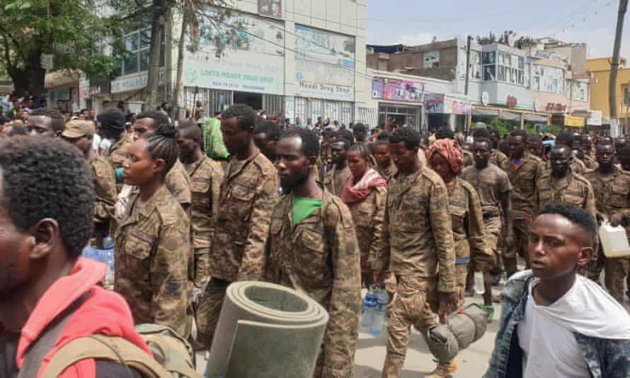 Ethiopian government soldiers and prisoners of war walk through the streets of Mekelle