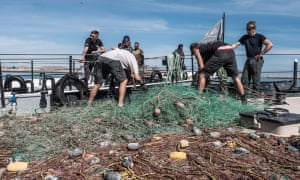 Men haul discarded fishing tackle from a boat on to a quay