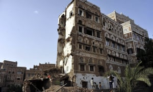 Yemenis stand near a historical building destroyed by Saudi-led coalition forces in Sana'a, Yemen