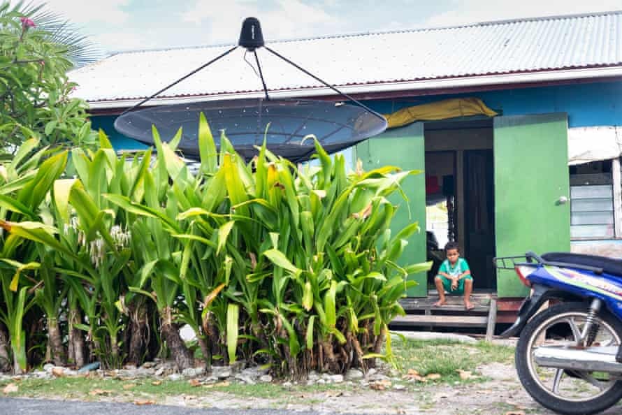 A young Tuvaluan boy sits outside a typical home in downtown Funafuti.