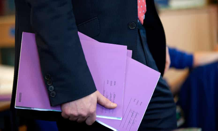 teacher in primary school class holding exercise books