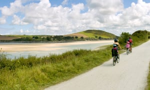 Two riders with children on a tag-along and in a child seat on the camel trail cycleway and footpath