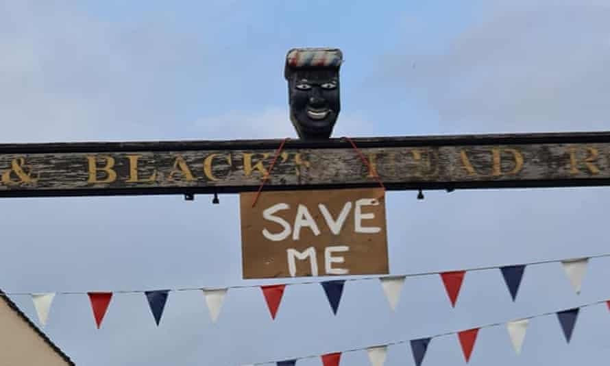 A sign saying 'Save Me' hanging below the bust before it was seized on Monday
