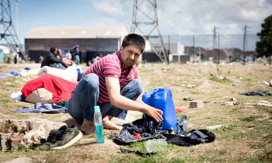 A refugee washes his clothes at a camp in Calais, France.