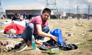 A refugee washing clothes on the ground at a Calais migrants' camp, France, in August 2017.