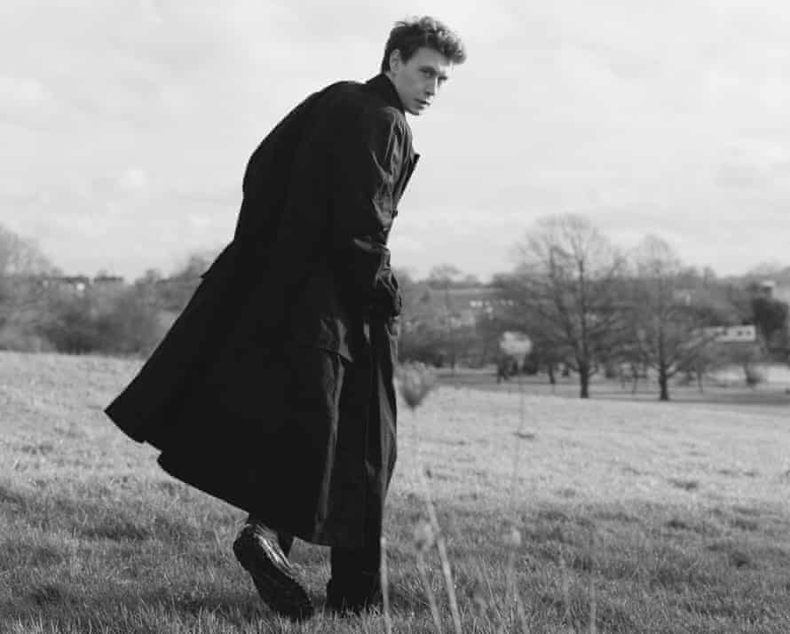 George MacKay, actor, looking back while walking across a field, January 2020