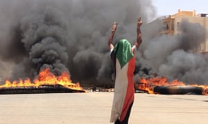 A protester in front of burning tyres and debris near Khartoum's army headquarters.