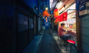Man eating alone at noodle bar