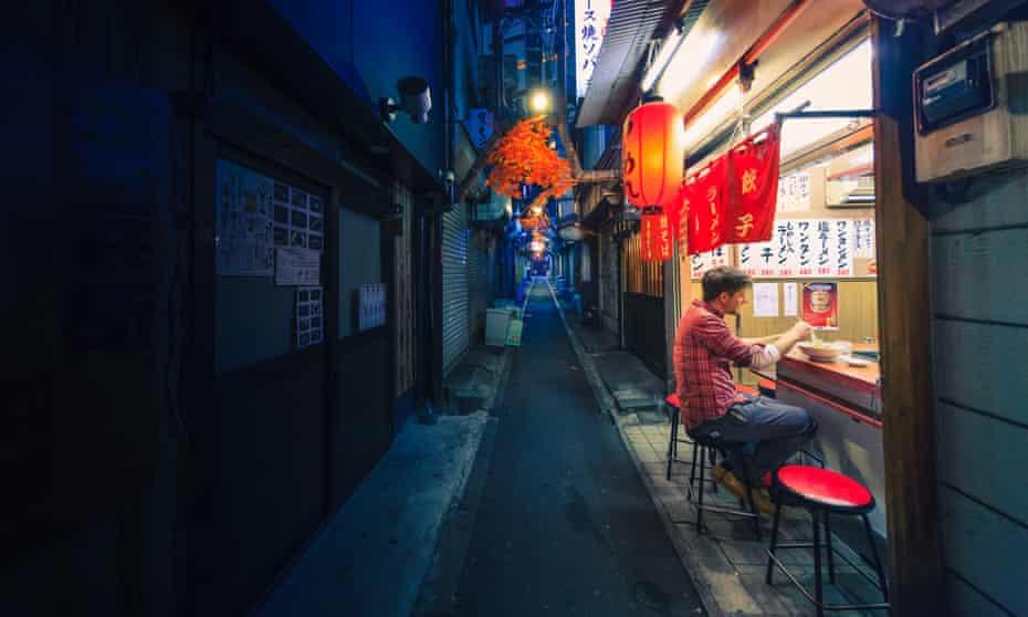 Man eating alone at noodle bar