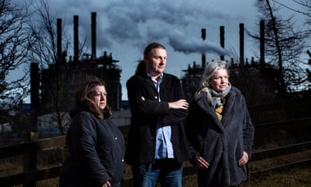 (from left) Linda Erskine, James Glen and Linda Holt stand against a backdrop of the Mossmorran petrochemical plant in Fife.