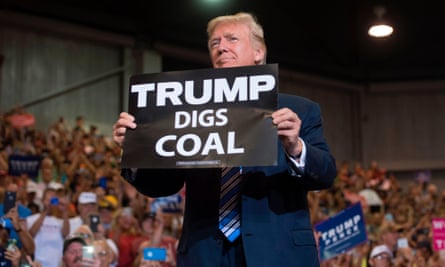 "Donald Trump holds up a ""Trump Digs Coal"" sign as he arrives to speak during a Make America Great Again Rally at Big Sandy Superstore Arena in Huntington, West Virginia, August 3, 2017."