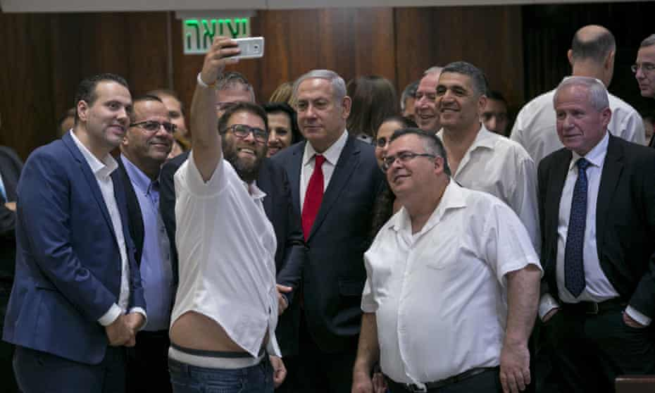 Knesset member Oren Hazan takes a selfie with Benjamin Netanyahu, centre, after the session that passed the contentious bill in Jerusalem.