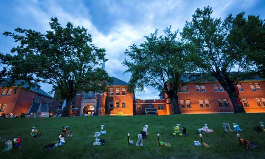 Pairs of children's shoes and toys at a memorial in front of the former Kamloops residential school, Canada's largest such facility.