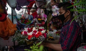 A worker decorates flowers for sale ahead of Valentine's Day in Kuala Lumpur.