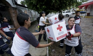 Red Cross volunteers load humanitarian aid boxes from a truck in the Pacific beach resort of Puerto Vallarta, Mexico, on Saturday.