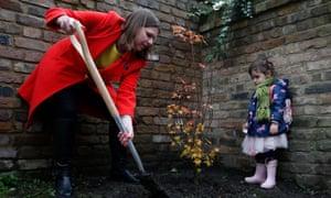 Jo Swinson plants a tree at Razumovsky Academy in Kensal Green as two-year-old Maya Litani watches on .