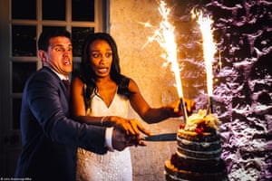Newlyweds look alarmed as they light fireworks on their wedding cake.